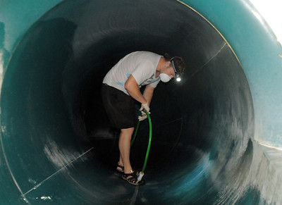 Lifeguard Shane Mortensen brings a water hose through the tunnel of a slide during the deep cleaning of the Paul Derda Recreation Center  on Wednesday.  August 24, 2011 staff photo/ David R. Jennings