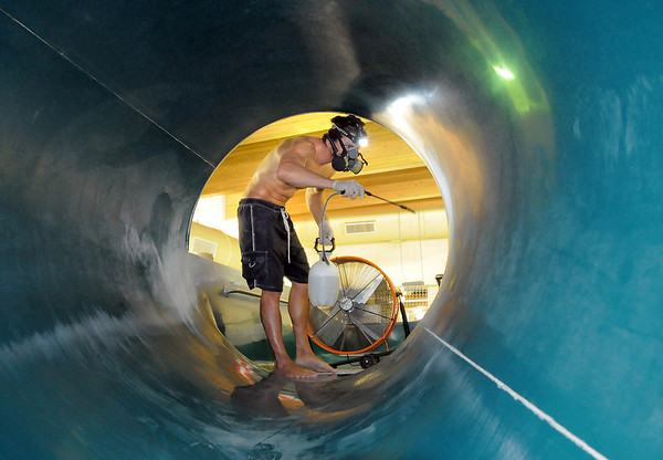 Lifeguard Carson Voss wears a mask to clean one of the water slides during the deep cleaning of the Paul Derda Recreation Center on Wednesday.<br /> <br /> August 24, 2011<br /> staff photo/ David R. Jennings