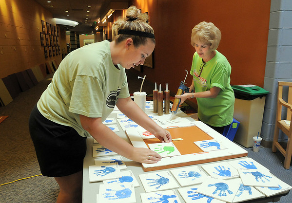 Brenda Wiegert, left, and Diane Sorge assemble the tile hand prints of the Early Learning children to be punted on the wall at the Paul Derda Recreation Center on Thursday.<br /> <br /> August 24, 2011<br /> staff photo/ David R. Jennings