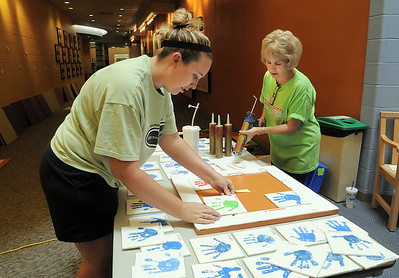 Brenda Wiegert, left, and Diane Sorge assemble the tile hand prints of the Early Learning children to be punted on the wall at the Paul Derda Recreation Center on Thursday.  August 24, 2011 staff photo/ David R. Jennings
