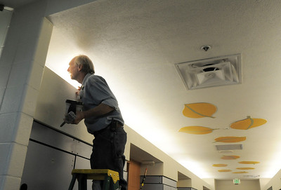 Ken Thomas checks his paint job of the ceiling in the hallway leading to the pool during the deep cleaning of the Paul Derda Recreation Center  on Wednesday.  August 24, 2011 staff photo/ David R. Jennings