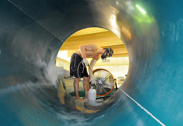 Carson Voss wears a mask to clean one of the water slides during the deep cleaning of the Paul Derda Recreation Center on Wednesday.<br /> August 24, 2011<br /> staff photo/ David R. Jennings