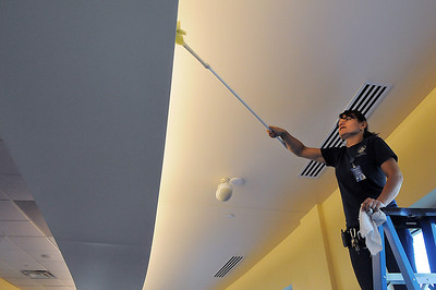 Rosa Cabral wipes dust from lights above the running track during the deep cleaning of the Paul Derda Recreation Center on Thursday.  August 24, 2011 staff photo/ David R. Jennings
