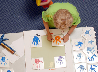 Diane Sorge glues tiles of hand prints made by the  children in the Early Learning Center for display on a wall of the Paul Derda Recreation Center during the deep cleaning of the center on Thursday.  August 24, 2011 staff photo/ David R. Jennings