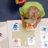 Diane Sorge glues tiles of hand prints made by the  children in the Early Learning Center for display on a wall of the Paul Derda Recreation Center during the deep cleaning of the center on Thursday.<br /> <br /> August 24, 2011<br /> staff photo/ David R. Jennings