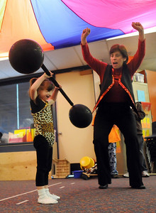Kaylie Bookout, as the strong girl, is encouraged by her teacher Dianne Goberis to lift the heavy weights during the Pee Wee Circus at Mountain View Elementary School on Friday.   March 18, 2010 Staff photo/David R. Jennings