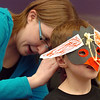 Library volunteer Kelsey Kalmbaca, 17, helps Evyn Bradley, 7, put on his penguin mask during Third Saturday Fun's Penguin Adventure at the Children's Library at Mamie Doud Eisenhower Public Library on Saturday. <br /> <br /> January 15, 2011<br /> staff photo/David R. Jennings