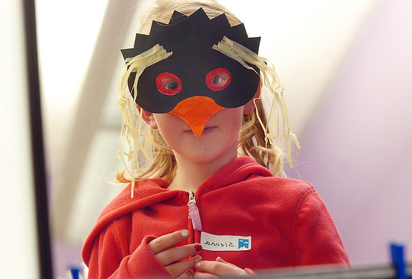 Sienna Cook, 7, looks at her reflection in a mirror while wearing a penguin mask during Third Saturday Fun's Penguin Adventure at the Children's Library at Mamie Doud Eisenhower Public Library on Saturday. <br /> <br /> January 15, 2011<br /> staff photo/David R. Jennings