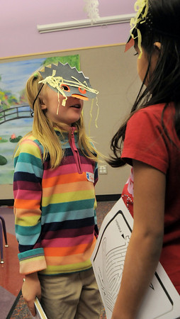 Teagan Bradley, 6, left, and Kaviya Chidambaram, 6, try to walk like penguins while wearing their masks during Third Saturday Fun's Penguin Adventure at the Children's Library at Mamie Doud Eisenhower Public Library on Saturday.  <br /> <br /> January 15, 2011<br /> staff photo/David R. Jennings