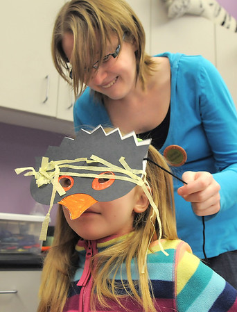 Teagan Bradley, 6, has volunteer Kelsey Kalmbach, 17, help put on  her penguin mask on during Third Saturday Fun's Penguin Adventure at the Children's Library at Mamie Doud Eisenhower Public Library on Saturday. <br /> <br /> January 15, 2011<br /> staff photo/David R. Jennings