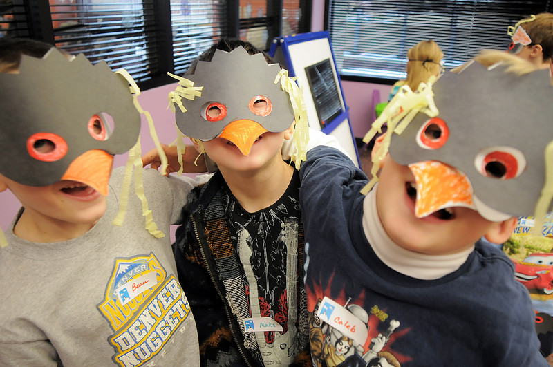 Beau Noland, 7, left, Maks Marko, 6, and Caleb Ellis, 7, show their penguin masks they made during Third Saturday Fun's Penguin Adventure at the Children's Library at Mamie Doud Eisenhower Public Library on Saturday.  <br /> <br /> January 15, 2011<br /> staff photo/David R. Jennings