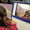 Joleen Jacobi, 6, looks in a mirror to see how her penguin mask looks during Third Saturday Fun's Penguin Adventure at the Children's Library at Mamie Doud Eisenhower Public Library on Saturday. <br /> <br /> January 15, 2011<br /> staff photo/David R. Jennings