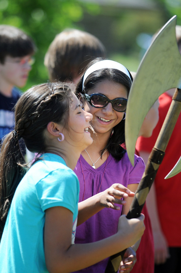 BE0704SWORD03<br /> Vanessa Cornejo, 10, left, and her sister Olivia Cornejo, 12, try to hold a battle ax during the sword fighting session at the Percy Jackson and Camp Half-Blood Mamie Doud eisenhower Public Library program on Wednesday at Community Park.<br /> <br /> June 30, 2010<br /> Staff photo/ David R. Jennings