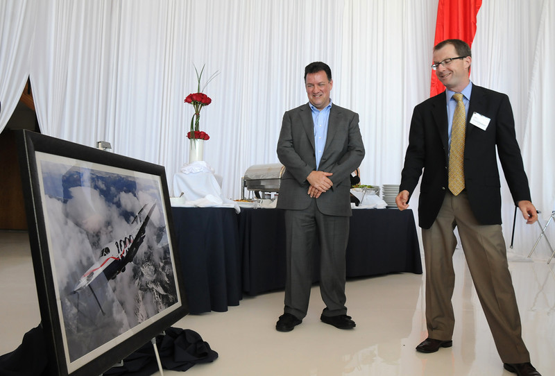 Pilatus CEO Thomas Bosshard, right, unveils a photograph of the 1000th PC-12 NG plane over the Swiss Alps owned by David Fountain, left,  during the celebration of the 1000th PC-12 NG aircraft at  Pilatus Aircraft's western hemisphere headquarters based at Rocky Mountain Metropolitan Airport in Broomfield on Thursday<br /> July 15, 2010<br /> Staff photo/ David R. Jennings
