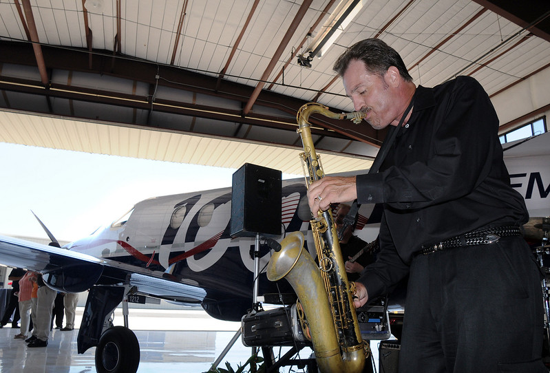 Steve Watts plays the sax with the band Dotsero during the celebration of the 1000th PC-12 NG aircraft at Pilatus Aircraft's western hemisphere headquarters based at Rocky Mountain Metropolitan Airport in Broomfield on Thursday.<br /> July 15, 2010<br /> Staff photo/ David R. Jennings