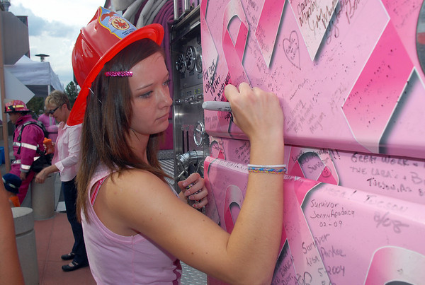 Alex Van Deboogaard signs a Pink Fire Truck in honor of the father of the coach of the Legacy High cheerleaders during the Pink Heals Tour  stop at the Village at FlatIron Crossing on Tuesday.<br /> Sept. 15, 2009<br /> Staff photo/David R. Jennings