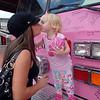 Brittany Orton, left, kisses her daughter Tessa Faye, 2, after posing on a Pink Fire Truck during the Pink Heals Tour stop at the Village at FlatIron Crossing on Tuesday.<br /> Sept. 15, 2009<br /> Staff photo/David R. Jennings