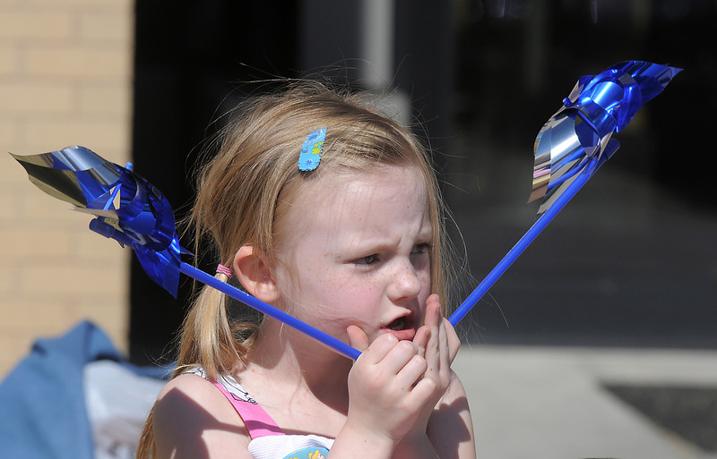 """Daneka Jones, 5, holds two pinwheelsto be """"planted"""" in the raised flower bed at Mamie Doud Eisenhower Public Library on Saturday for National Child Abuse Prevention Month.<br /> April 2, 2011<br /> staff photo/David R. Jennings"""