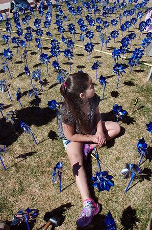 "Alexis Jimenez, 8, is surrounded by some 300 pinwheels in the raised flower bed at Mamie Doud Eisenhower Public Library on Saturday ""planted"" for National Child Abuse Prevention Month.<br /> <br /> April 2, 2011<br /> staff photo/David R. Jennings"