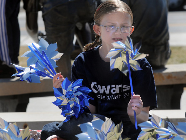 "Rylie James, 9, looks at pinwheels to be ""planted""  in the raised flower bed at Mamie Doud Eisenhower Public Library on Saturday for National Child Abuse Prevention Month.<br /> April 2, 2011<br /> staff photo/David R. Jennings"