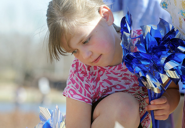 "Kaitlyn Torkelson, 8, holds pinwheels while helping to ""plant"" 300 pinwheels in the raised flower bed at Mamie Doud Eisenhower Public Library on Saturday for National Child Abuse Prevention Month.<br /> April 2, 2011<br /> staff photo/David R. Jennings"