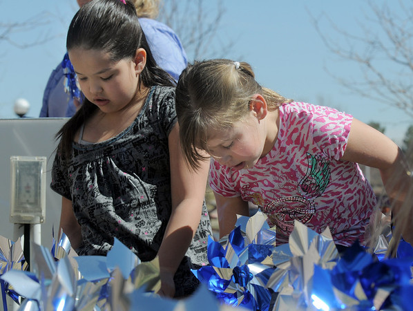 "Alexis Jimenez, 8, and Kaitlyn Torkelson, 8,  ""plant"" some of the 300 pinwheels in the raised flower bed at Mamie Doud Eisenhower Public Library on Saturday for National Child Abuse Prevention Month.<br /> <br /> April 2, 2011<br /> staff photo/David R. Jennings"