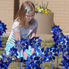 "Joy Putnan, 9, ""plants"" one of the 300 pinwheels in the raised flower bed at Mamie Doud Eisenhower Public Library on Saturday for National Child Abuse Prevention Month.<br /> April 2, 2011<br /> staff photo/David R. Jennings"
