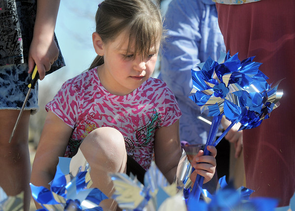 "xx helps ""plant"" 300 pinwheels in the raised flower bed at Mamie Doud Eisenhower Public Library on Saturday.<br /> April 2, 2011<br /> staff photo/David R. Jennings"