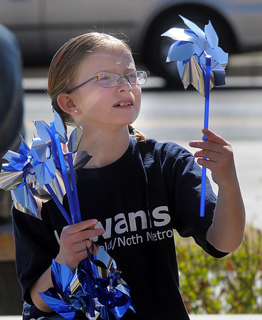 """Rylie James, 9, looks at pinwheels to be """"planted""""  in the raised flower bed at Mamie Doud Eisenhower Public Library on Saturday for National Child Abuse Prevention Month.<br /> <br /> April 2, 2011<br /> staff photo/David R. Jennings"""