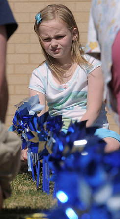 """Joy Putnan, 9, looks down a row of """"planted"""" pinwheels in the raised flower bed at Mamie Doud Eisenhower Public Library on Saturday for National Child Abuse Prevention Month.<br /> <br /> April 2, 2011<br /> staff photo/David R. Jennings"""