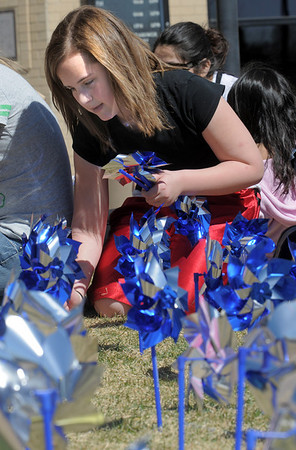 "Aisha Gray, 12, places pinwheels in the ground while helping to ""plant"" 300 pinwheels in the raised flower bed at Mamie Doud Eisenhower Public Library on Saturday for National Child Abuse Prevention Month.<br /> <br /> April 2, 2011<br /> staff photo/David R. Jennings"