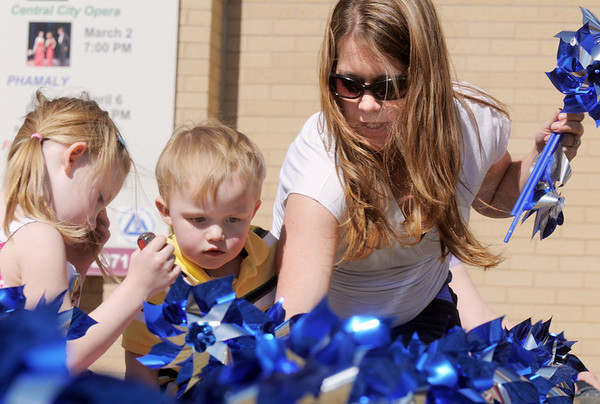 """Jessica Jones, right, with her children Daneka, 5 1/2 and Owen, 3, help """"plant"""" some of the 300 pinwheels in the raised flower bed at Mamie Doud Eisenhower Public Library on Saturday for National Child Abuse Prevention Month.<br /> <br /> April 2, 2011<br /> staff photo/David R. Jennings"""