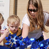 "Jessica Jones, right, with her children Daneka, 5 1/2 and Owen, 3, help ""plant"" some of the 300 pinwheels in the raised flower bed at Mamie Doud Eisenhower Public Library on Saturday for National Child Abuse Prevention Month.<br /> <br /> April 2, 2011<br /> staff photo/David R. Jennings"