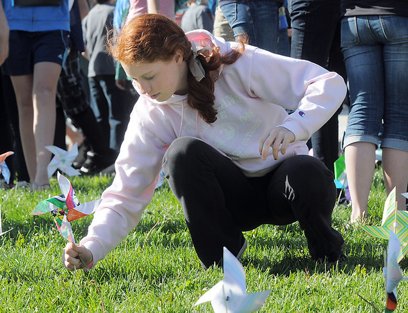Aspen Creek K-8 eighth grader Taylor Lindquist plants her pinwheel for the Pinwheels for Peace project on Wednesday at the school. Students from all grades planted pinwheels making the shape of peace signs.<br /> September 21, 2011<br /> staff photo/ David R. Jennings