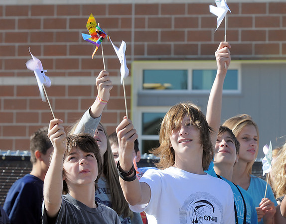 Ben Cameron, left, and Chad Britton, eighth graders at Aspen Creek K-8 school, raise pinwheels in the air for the Pinwheels for Peace project on Wednesday at the school. Students from all grades planted pinwheels in the shape of peace signs.<br /> September 21, 2011<br /> staff photo/ David R. Jennings