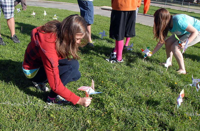 Jenna Ireland, eighth grader at Aspen Creek K-8 school, plants her pinwheels she made for the Pinwheels for Peace project on Wednesday at the school. Students from all grades planted pinwheels in the shape of peace signs.<br /> September 21, 2011<br /> staff photo/ David R. Jennings