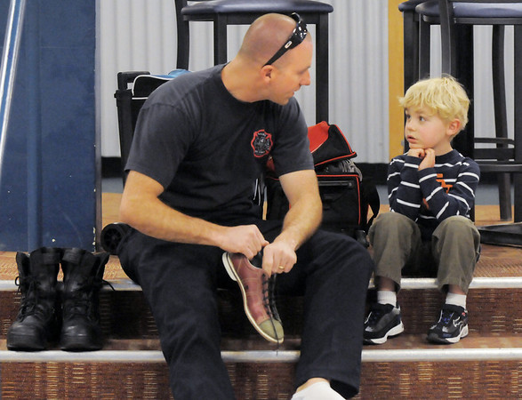North Metro Fire Rescue firefighter Travis Hayden, left, talks with his son Owen, 4, while changing into bowling shoes for  the Police vs. Fire Bowling Tournament for A Precious Child at Chippers Lanes Bowling Alley on Sunday.<br /> April 10, 2011<br /> staff photo/David R. Jennings