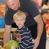 North Metro Fire Rescue firefighter Travis Hayden, left, helps his son Owen, 4, with bowling during the Police vs. Fire Bowling Tournament for A Precious Child at Chippers Lanes Bowling Alley on Sunday.<br /> April 10, 2011<br /> staff photo/David R. Jennings