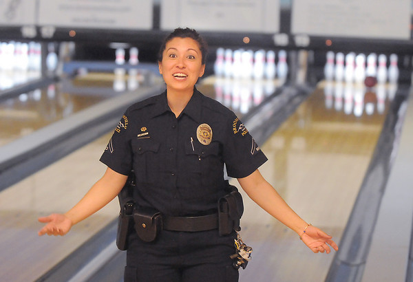 Broomfield Police officer Bernadette Espinoza talks to her team while the ball is still going down the lane during the Police vs. Fire Bowling Tournament for A Precious Child at Chippers Lanes Bowling Alley on Sunday.<br /> April 10, 2011<br /> staff photo/David R. Jennings