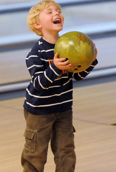 Owen Hayden, 4, laughs as he carries the ball to the lane to bowl for North Metro Fire Rescue during the Police vs. Fire Bowling Tournament for A Precious Child at Chippers Lanes Bowling Alley on Sunday.<br /> April 10, 2011<br /> staff photo/David R. Jennings