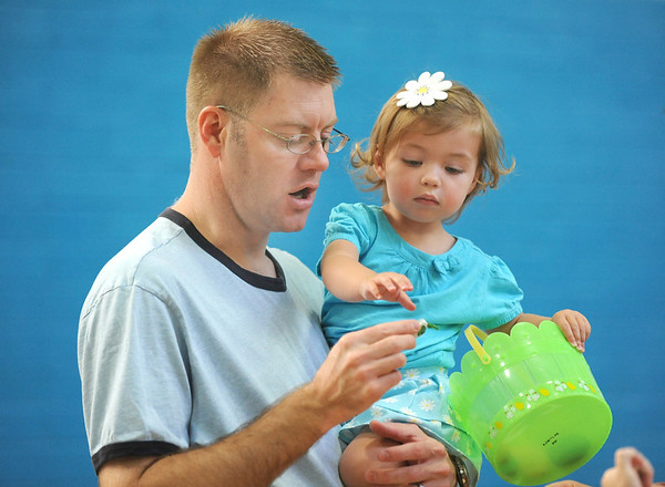 Avery Weihing, 20 months-old gets a little help from her father, C.J., with a prize from a plastic egg during the Preschool Easter Party at the Broomfield Community Center on Thursday.<br /> April 5, 2012 <br /> staff photo/ David R. Jennings