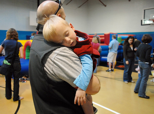 Liam Wright, 2, being held by his father Dan, sleeps during the Preschool Easter Party at the Broomfield Community Center on Thursday.<br /> April 1, 2010<br /> Staff photo/David R. Jennings