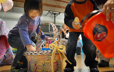Kate Tsai, 3 1/2, reaches in Flopsy the Bunny's basket for plastic eggs during the Preschool Easter Party at the Broomfield Community Center on Thursday. April 1, 2010 Staff photo/David R. Jennings