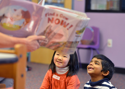 """Lindsay Uba, 5, left, and Pavan Gunasinghe, 4, look at the pictures in the book """"Find a Cow NOW!""""  read by children's librarian Susan Person during the preschool story time at the Mamie Doud Eisenhower Public Library on Thursday. December 27, 2012 staff photo/ David R. Jennings"""