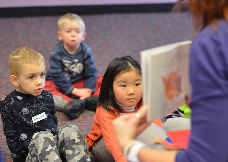 Mason Monroe, 4, left, Jack Smith, 4, and Lindsay Uba, 5  listen to children's librarian Susan Person read a book during the preschool story time at the Mamie Doud Eisenhower Public Library on Thursday.<br /> December 27, 2012<br /> staff photo/ David R. Jennings