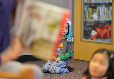 Ian Dolber, 4, watches and listens at a distance to children's librarian Susan Person read a book during the preschool story time at the Mamie Doud Eisenhower Public Library on Thursday. December 27, 2012 staff photo/ David R. Jennings