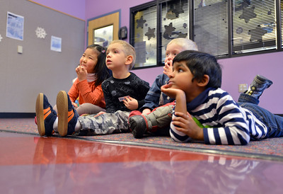 Lindsay Uba, 5, left, Mason Monroe, 4, Jack Smith, 4, and Pavan Gunasinghe, 4,  listen to children's librarian Susan Person read a book during the preschool story time at the Mamie Doud Eisenhower Public Library on Thursday. December 27, 2012 staff photo/ David R. Jennings