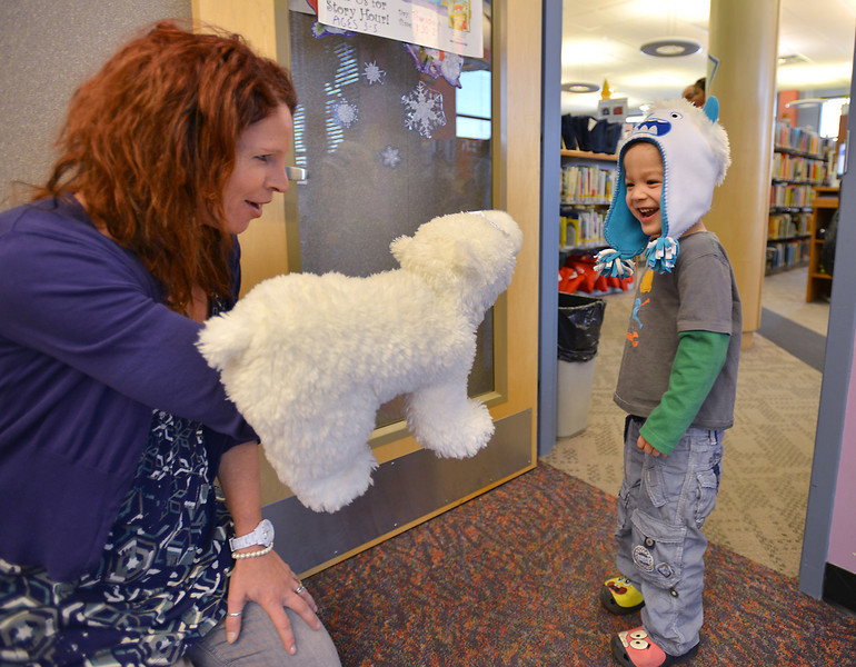 Children's librarian Susan Person, left, tries to get Ian Dolber, 4, to hug her bear puppet after reading during preschool story time at the Mamie Doud Eisenhower Public Library on Thursday.<br /> December 27, 2012<br /> staff photo/ David R. Jennings