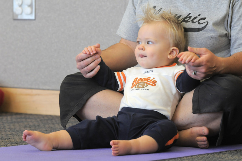 Conor Betts, 16 months-old, moves with his mother Kelleigh during the Preschool Yoga/Movement session taught by Sara Guenther at the Mamie Doud Eisenhower Public Library on Saturday.<br /> <br /> November 18, 2011<br /> staff photo/ David R. Jennings