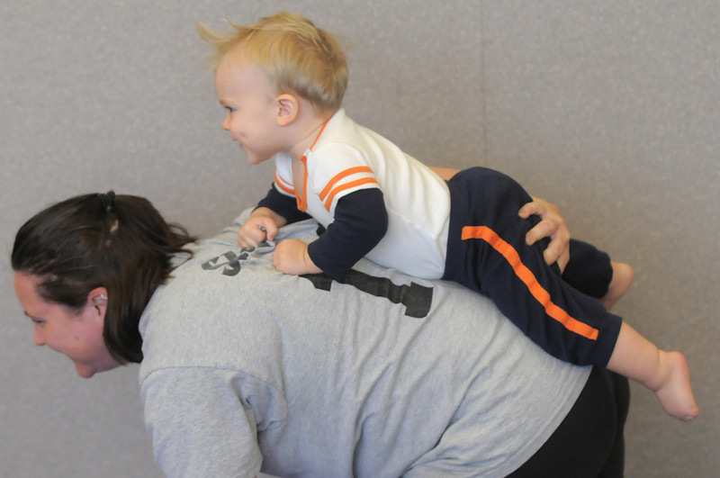 Kelleigh Betts carries her son Conor, 16 months-old on her back while pretending to be a lion during the Preschool Yoga/Movement session taught by Sara Guenther at the Mamie Doud Eisenhower Public Library on Saturday.<br /> <br /> November 18, 2011<br /> staff photo/ David R. Jennings
